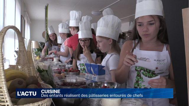 Des enfants réalisent des pâtisseries entourés de chefs